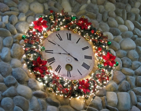 decor: This holiday image is a large clock decorated with Christmas lights, wreath and other decor, hung on a rock wall
