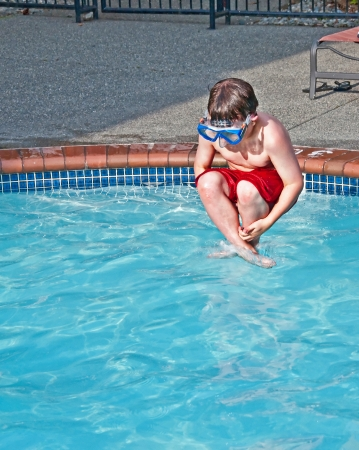 This 8 year old Caucasian boy is wearing a swimming mask, while doing a cannon ball, mid air into a pool of water Stock Photo