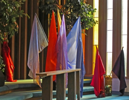 shimmery: This is several sheer and shimmery colored, plain flags sitting next to some stained glass windows indoors with sunlight hitting them