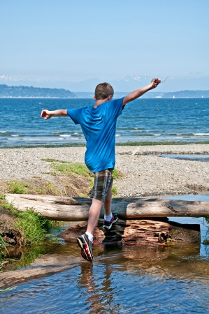 13 year old: This 13 year old Caucasian boy is running and jumping while playing at the beach   His arms are held high in the air, ready to conquer the world   Full body, rear view in vertical format  Stock Photo