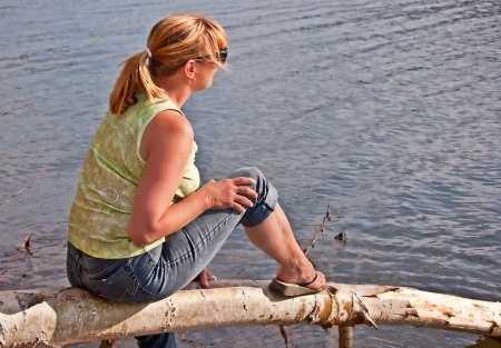 This middle aged Caucasian woman with blond hair in a pony tail, is sitting on a log and relaxing at a lake photo