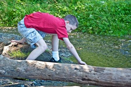 chłopięctwo: Ten pre-teen Kaukaski chłopiec bawi się poza pobliżu potoku w lesie, pochylając się i chodzenia na dziennik ociera łokieć wyświetla klasyczny chwilę dzieciństwa w młodości