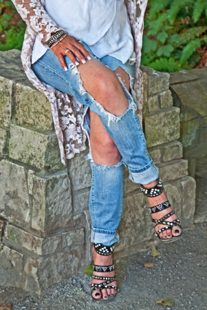 ripped jeans: This woman is sitting on a stone wall wearing torn jeans with sandals that lace up and pedicured feet   Waist down front view, legs crossed  Stock Photo