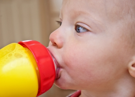 closeup of a toddler girl drinking milk out of a sippy cup  photo