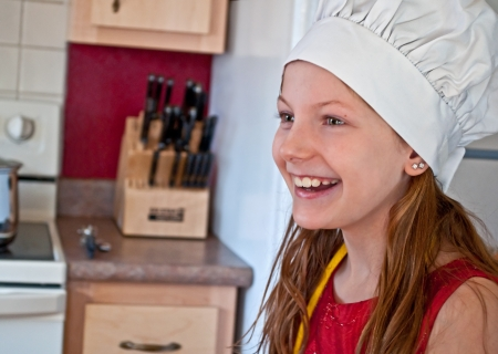 This 10 year old Caucasian girl is happy and smiling in the kitchen, while wearing a white chef photo