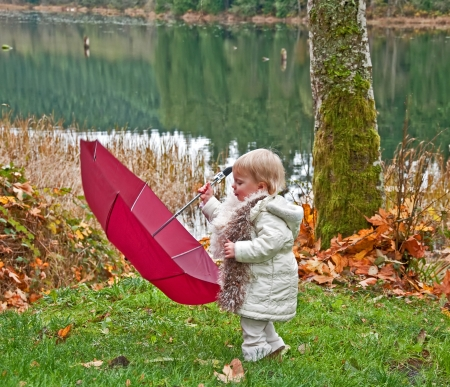 brisk: This young toddler girl wearing white and a scarf has her hands full with a big burgundy colored umbrella   She is outdoors in the fall next to a lake enjoying a brisk day