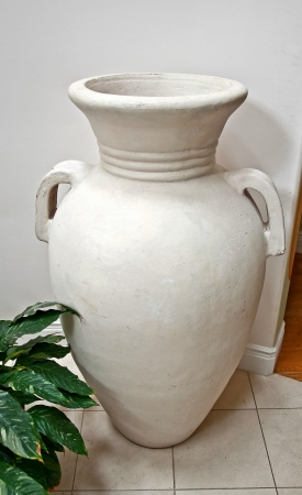 home related: This home related object is a very large, white pottery vase in an interior setting