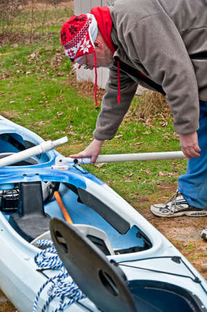 This middle aged man with a hat is bent over working on a kayak in a home setting, doing repairs and modifications of this small boat  Stock Photo - 18457235