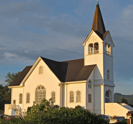 country church: This white church is a historic landmark in Conway, Washington on Fir Island   Sunset is hitting against a darker sky background  Stock Photo