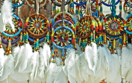 beaded: This is a group of Native American beaded dream catchers, with white feathers at the bottom
