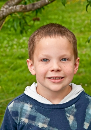 This cute little 8 year old Caucasian boy is smiling outdoors   He is wearing a plaid type shirt, has blue eyes and freckles   It photo