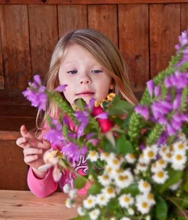 This sweet 4 year old girl is behind a cut flower bouquet, arranging the flowers   Flowers are intentionally blurred to emphasize the child
