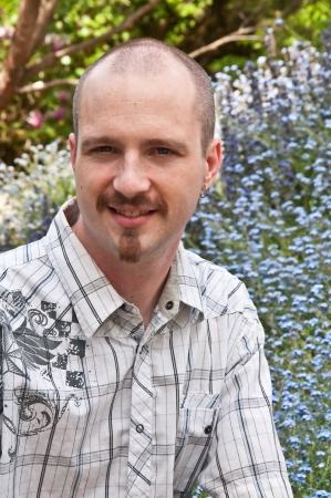 This is a young Caucasian man outdoors in a portrait head and shoulders shot   He has a bald, shaved head, goatee, blue eyes, and is smiling  photo