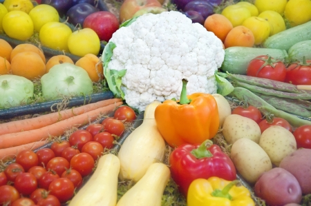 This is a circular display of various fruits and vegetables, with a white cauliflower as the center   Tomatoes, carrots, squash, potates, apricots, apples, and peppers are in this food image  Stock Photo
