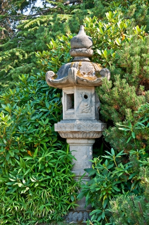evergreen trees: This concrete pole is a Japanese style decor in a garden setting with plants and various evergreen trees   Peaceful and quiet place  Stock Photo
