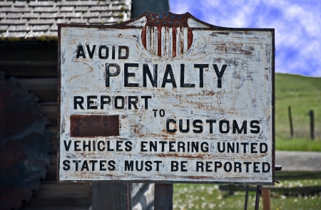 This is a vintage, turn of the century sign of the United States custom, border crossing   Background is a vintage building and tools  Standard-Bild