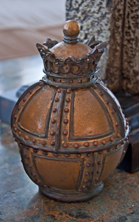 antique vase: This home decor object is an antique metal small vase   It has many details and textures that make it a beautiful object