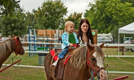 peuter meisje is het berijden van een eerste pony rijden met haar moeder lopen naast haar Stockfoto