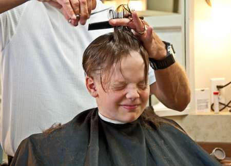 This 9 year old Caucasian boy is getting his hair cut from quite long to very short   Has a facial expression that conveys lots of emotion  photo