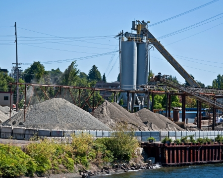 gravel pit: This is an industrial image of a gravel pit with a large silo and belts, along with large piles of various grades of gravel  Stock Photo