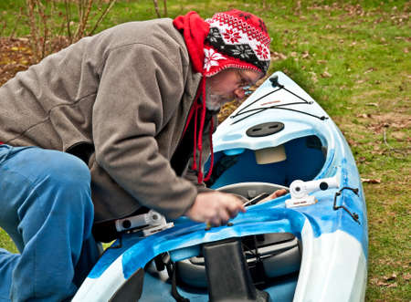This Caucasian, middle age man is working on a kayak in the yard during off season   He photo