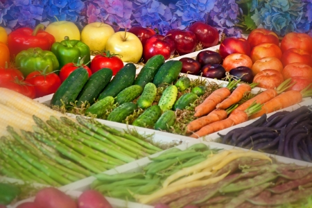 This is a pretty display of organic produce, fresh vegetables and fruits, lined with blue hydrangea flowers in the back   Cucumbers and carrots are the emphasized vegetables, there are also, apples, green and red bell peppers, corn on the cob, asparagus,  photo