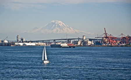 This landscape is of Mt Rainier, snow covered in Washington state   Upon Puget Sound water is a sailboat in the foregound and part of Seattle skyline in the foreground as well  photo