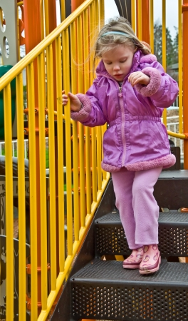 bajando escaleras: Este niño de 4 años, raza blanca bajando escaleras en el equipo del patio en un día frío y ventoso Ella