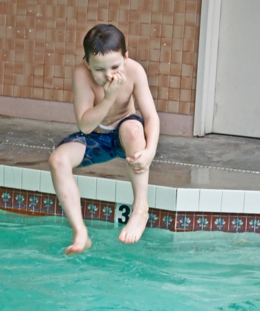 This 7 year old Caucasian boy is doing a cannon ball mid air into a swimming pool, while plugging his nose  photo