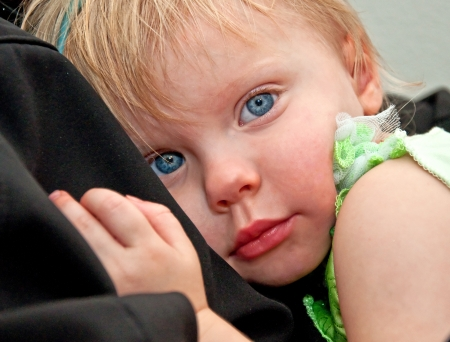 This cute 2 year old girl toddler with big blue eyes, is tired as she photo