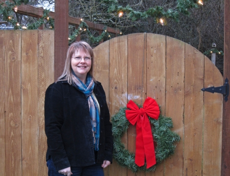 This is a portrait of a middle aged Caucasian woman near a wooden gate with a Christmas wreath on it outdoors   Model is a Caucasian with blondish shoulder length hair, wearing a plaid scarf and black coat