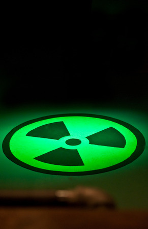 This is the symbol for the chemical radium, painted on a floor with green lights shinning on it against a black wall in vertical format Stock Photo - 28069101