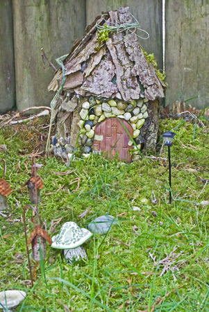 This is a miniature fairy garden scene, rustic with a small home made of wood and stones, with tiny garden lights and trinkets along the path