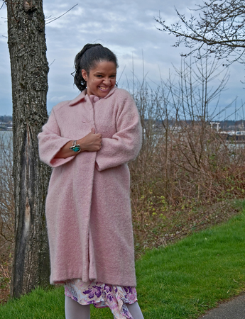This pretty multi-ethnic woman is in a playful pose wearing a long pastel pink coat outsdoors on an early spring day.  Background is the ocean which is intentionally blurred to emphasize subject.  Photo is vertical orientation. photo