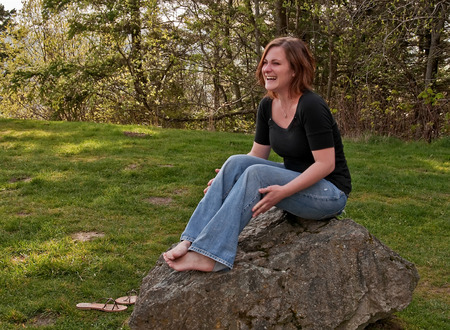 This image is a young Caucasian woman wearing blue jeans and a black shirt, laughing while sitting barefoot on a large rock.  Very natural looking, outdoors portrait.