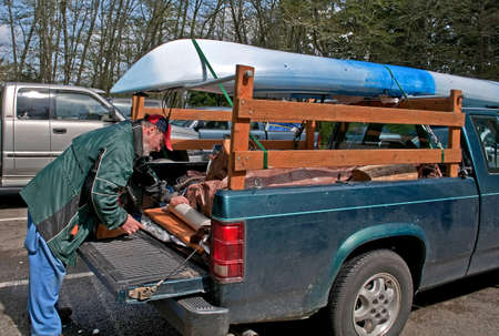 This middle aged Caucasian man is preparing the back of his truck with camping gear with a kayak loaded on top in readiness for a camping trip. photo