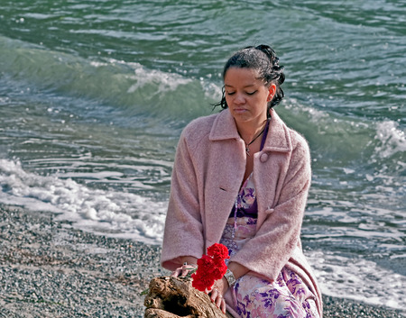 This pretty multi racial woman in her thirties is wearing a pink coat and holding red carnation flowers at the beach.  Her mood is one of quiet reflection and introspection.