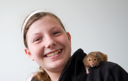 This is a cute Caucasian 12 year old girl with a hamster on her shoulder.  She's happy and smiling with her pet. 写真素材