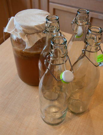 This is a still life a homemade kombucha in a gallon size jar with empty glass bottles ready to be filled.  Healthy probiotic drink.