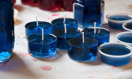 Blue tealight candles being made on a chandlers candle making bench in this craft hobby still life.  Liquid blue wax with red and yellow candles in background.