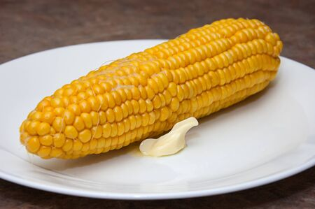 Corn on the cob with melted butter with the pat of butter part way melted on  a white plate in the food photo.
