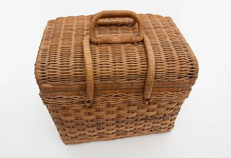 Wicker picnic basket isolated on light background with a closed lid.  Light tan object home related.