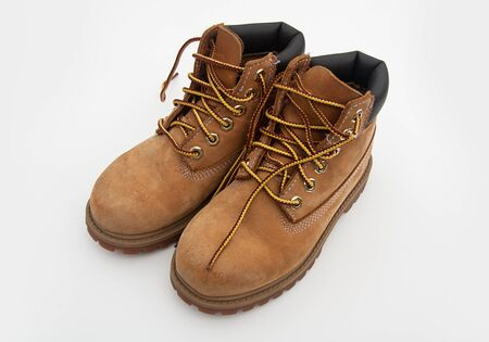 Pair of hiking boots tan colored with boot laces untied, isolated on light background. 版權商用圖片