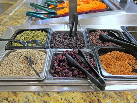 Salad bar toppings seeds and raisins. Dried cranberries, pepitas or pumpkin seeds, sunflower seeds and bacon crumbles in metal containers in this food photo.