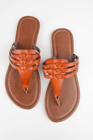 Womens pair of brown leather flat summer sandals isolated on a light background.  Casual footwear fashion accessory shoes.