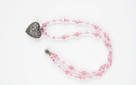 Pink beaded jewelry necklace with a heart shaped embellishment, isolated on a light background. Style for women fashion accessory.