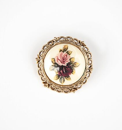 Jewelry vintage brooch with roses and gold ornate design around the edges of this antique pin isolated on a light background.  Fashion accessory object still life. Archivio Fotografico