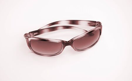 Sunglasses isolated on light background in sepia tones.  High gloss shiny metal effect in this pair of eyeglasses for summer fashion accessory, cool shades.