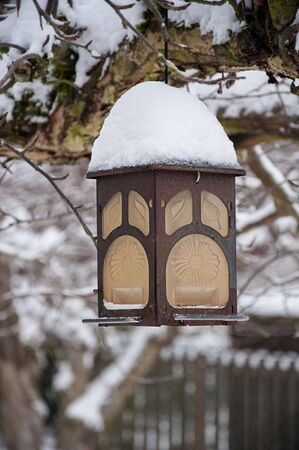 Decorative outdoor lantern in snow is brass object hanging from a tree covered with many inches of freshly fallen snow in winter.