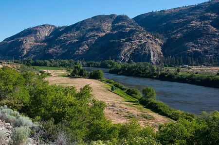 Landscape valley river Okanogan River near Omak Washington as the water weaves through the valley in between mountains and rural fields.  Okanogan Valley in Washington state.